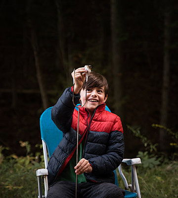 Young boy taking a marshmallow off of a metal stick outdoors. - p1166m2214645 by Cavan Images