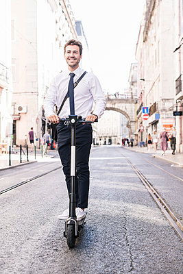 Happy young businessman riding e-scooter in the city, Lisbon, Portugal - p300m2144673 by Uwe Umstätter