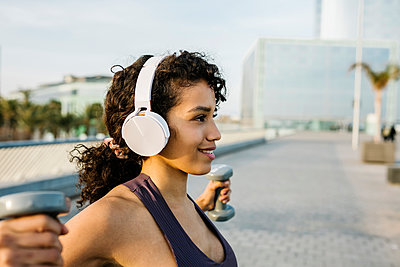 Smiling sportswoman listening music through headphones while exercising with dumbbell on footpath - p300m2277724 by Xavier Lorenzo