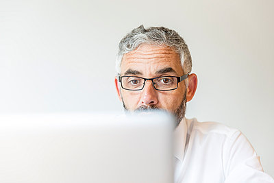 Portrait of astonished businessman working at laptop - p300m975239f by Martin Benik