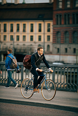 Full length of businessman riding bicycle on bridge - p426m2145593 by Maskot