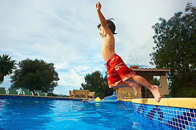 Young boy jumping into swimming pool - p42912018f by Frank and Helena