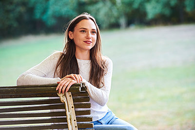 Smiling young woman sitting on bench in park - p623m2294794 by Eric Audras