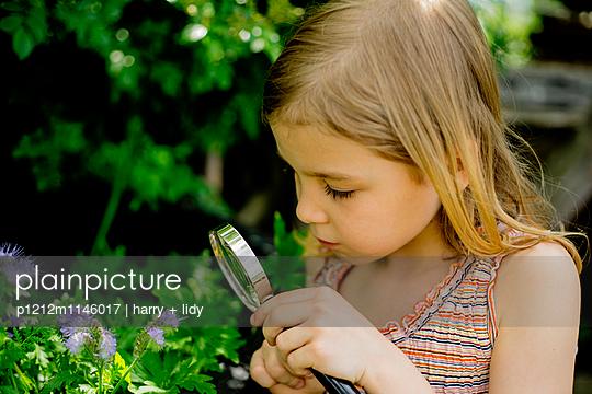 Mädchen mit Lupe im Garten - p1212m1146017 von harry + lidy