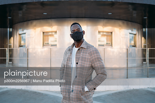 Fashionable man with protective face mask standing against building - p300m2256967 by Manu Padilla Photo