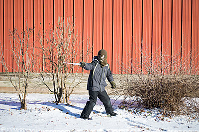 Boy playing with icicle - p1169m2108451 by Tytia Habing