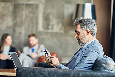 Businessman using laptop and smartphone in hotel lobby - p300m2171388 by Zeljko Dangubic
