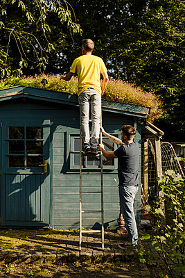 Father standing on ladder being supported by son in front of house - p300m2275048 by Gustafsson