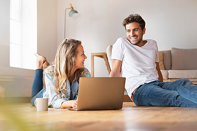 Relaxed woman with laptop looking at smiling boyfriend at home - p300m2276585 by Steve Brookland