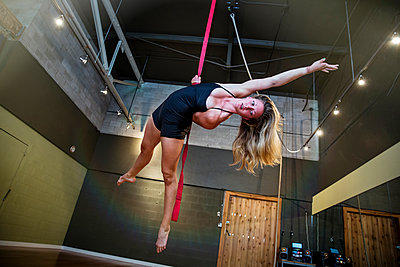 Caucasian acrobat hanging from ropes in studio - p555m1412616 by Inti St Clair photography