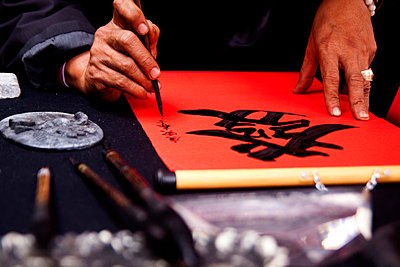 Calligraphers painting chinese characters close to the Temple of Literature in Hanoi; Vietnam. - p9340090 by Dominic Blewett
