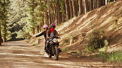 Exuberant young woman riding motorcycle on dirt road in woods - p1023m1156427 by Paul Bradbury