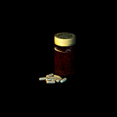 Pills and bottle on black background - p1072m954954f by Katerina Makasi