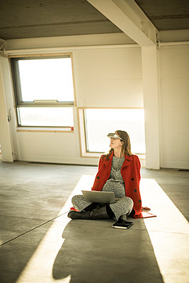 Pregnant busnesswoman sitting on floor of new office rooms, using VR goggles and laptop - p300m2104161 by Malte Jäger