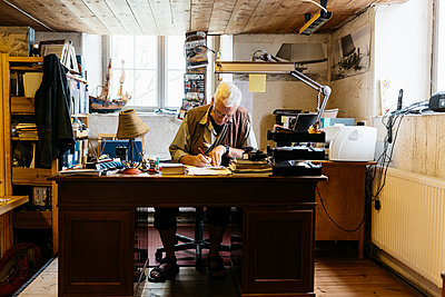 Rope maker sitting at desk in his shop - p352m2041426 by Folio Images
