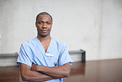 Portrait of confident mid adult male nurse standing with arms crossed in corridor at hospital - p426m2018932 by Maskot