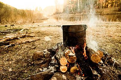 Pot cooking on campfire in rural field - p555m1411154 by Aleksander Rubtsov