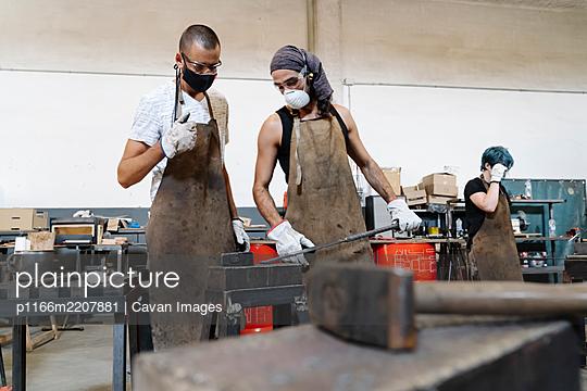 Serious men in aprons in workshop - p1166m2207881 by Cavan Images