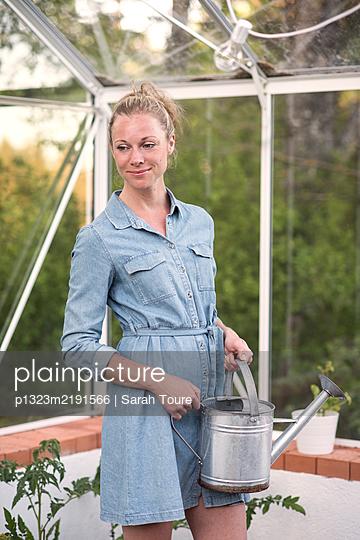 Woman gardening in her greenhouse  - p1323m2191566 von Sarah Toure
