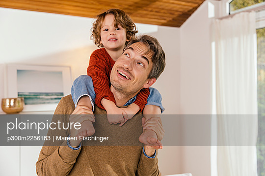 Father carrying daughter on shoulders at home - p300m2256183 by Mareen Fischinger