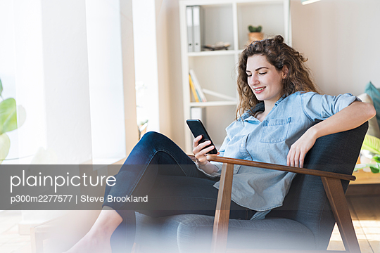 Smiling woman using smart phone while relaxing on chair at home - p300m2277577 by Steve Brookland