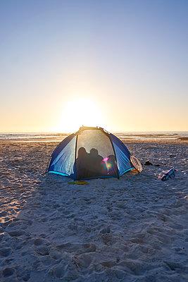 Silhouette family inside tent on sunny sunset beach - p1023m2200832 by Trevor Adeline