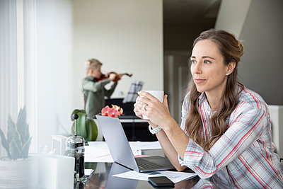 Thoughtful woman drinking coffee, working from home while son practices violin in background - p1192m2088269 by Hero Images