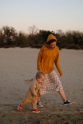 Woman with baby playing on beach - p1363m2142784 by Valery Skurydin