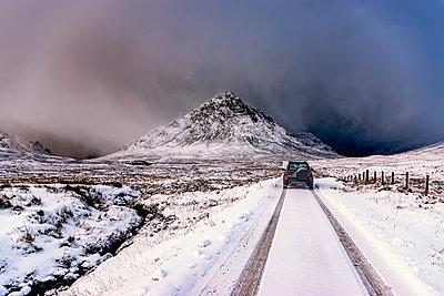 UK, Scotland, Glencoe, Buachaille Etive Mor, Four wheel drive vehicle in winter - p300m1228399 by Scott Masterton