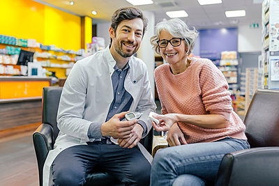 Portrait of smiling pharmacist and customer with blood sugar meter in pharmacy - p300m1549472 by Mareen Fischinger