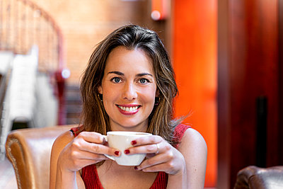 Portrait of smiling young woman with cup of coffee - p300m2131670 by VITTA GALLERY