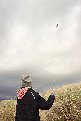 Rear view of boy flying kite against cloudy sky - p301m1180720 by Marc Volk