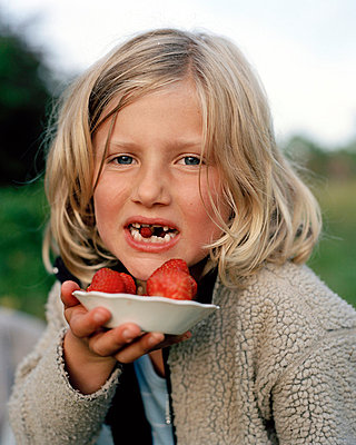 Girl with a wild strawberry between her teeth holds a plate with strawberries Öland Sweden. - p31216723f by Ulf Huett Nilsson