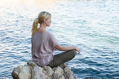 Woman meditating at sea - p312m957130f by Helen Karlsson