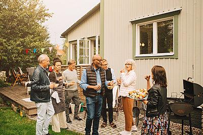 Active senior men and women enjoying dinner party at back yard - p426m2194888 by Maskot