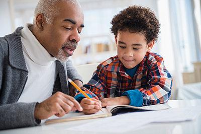 Mixed race grandfather helping grandson do homework - p555m1413055 by JGI/Jamie Grill