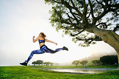 Mixed race woman running near lake - p555m1532668 by Peathegee Inc