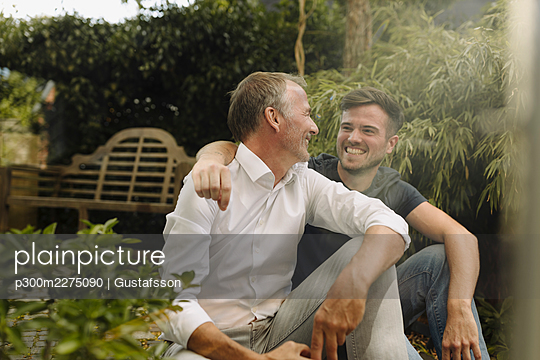 Smiling son and father looking at each other while sitting in backyard - p300m2275090 by Gustafsson