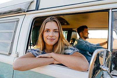 Portrait of smiling woman leaning out of window of a camper van with man driving - p300m2058856 von Gustafsson