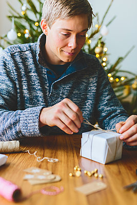 Finland, Man wrapping christmas gifts - p352m2205906 by Eija Huhtikorpi