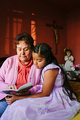 Hispanic grandmother and granddaughter ready book on bed - p555m1409594 by Shestock