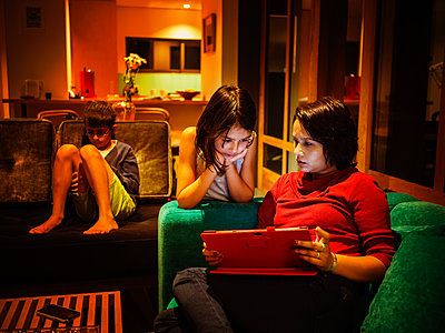 Family relaxing together in living room - p555m1420642 by Donald Iain Smith
