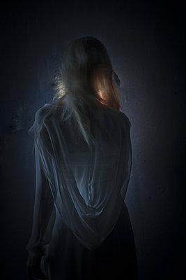 junge frau von hinten gesehen im dunkeln - p627m1035220 von Chris Keller