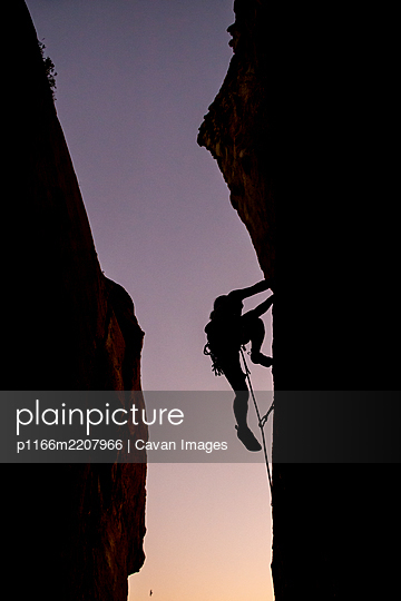 Beautiful view to silhouette of man climbing during sunset - p1166m2207966 by Cavan Images