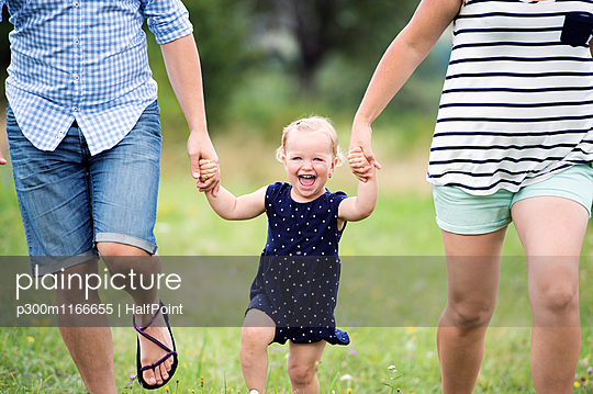 Laughing toddler girl holding hands of parents while running - p300m1166655 by HalfPoint