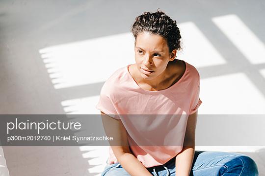 Woman sitting in sunlight, thinking - p300m2012740 von Kniel Synnatzschke