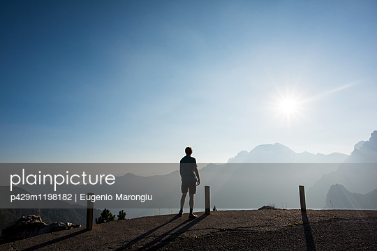 Rear view of man looking at view of mountains, Passo Maniva, Italy - p429m1198182 by Eugenio Marongiu