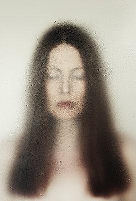 Frau mit geschlossenen Augen hinter einer nassen Scheibe - p1574m2183645 von manuela deigert