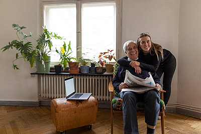 Portrait of happy young woman and senior man with newspaper at home - p300m2120170 by Gustafsson