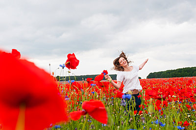 Happy beautiful woman running on poppy field against cloudy sky - p300m2197485 by Daniel Ingold
